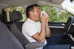 Homem que sneezing no carro Fotos de Stock Royalty Free