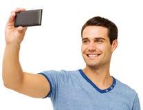 Homem que sorri ao fotografar através do telefone esperto imagem de stock royalty free