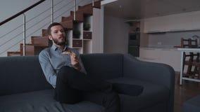 Homem que sorri, apreciando a pizza e sentando-se em casa video estoque