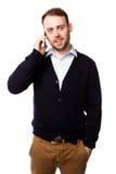 Homem que sorri como conversa em seu telefone celular Fotos de Stock