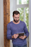 Homem que sorri como está de leitura seu tabuleta-PC Foto de Stock