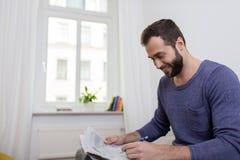 Homem que sorri como faz anotações em um jornal Fotos de Stock Royalty Free