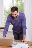 Homem que sorri como lê uma mensagem em seu portátil Fotografia de Stock Royalty Free