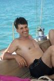 Homem que sorri no barco de vela Fotos de Stock Royalty Free