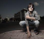 Homem que squatting na rua Fotografia de Stock Royalty Free