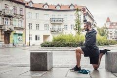 Homem que streching seus pés na cidade Fotografia de Stock
