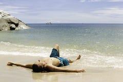 Homem que sunbathing na praia foto de stock