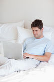 Homem que surfa o Internet na cama Fotografia de Stock Royalty Free