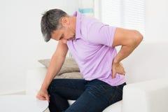 Homem que tem a dor lombar ao sentar-se no sofá fotos de stock