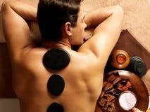 Homem que tem a massagem de pedra no salão de beleza dos termas Foto de Stock