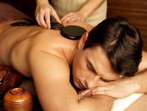 Homem que tem a massagem de pedra no salão de beleza dos termas Fotos de Stock Royalty Free