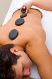 Homem que tem a massagem de pedra quente Foto de Stock