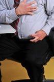 Homem que tem o cardíaco de ataque em sua mesa Imagens de Stock