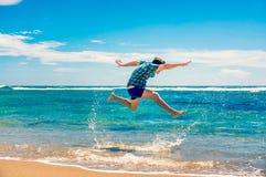 Homem que tem o divertimento na praia Fotografia de Stock