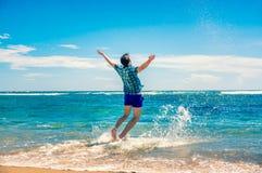 Homem que tem o divertimento na praia Imagens de Stock