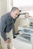 Homem que tem o problema com a fotocopiadora no escritório Fotografia de Stock Royalty Free