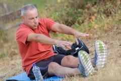 Homem que tenta alcançar os pés foto de stock royalty free
