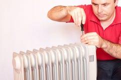 Homem que tenta reparar um radiador fotografia de stock royalty free