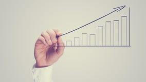 Homem que tira um gráfico de barra de ascensão Imagens de Stock