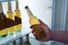 Homem que toma a cerveja de um refrigerador Fotografia de Stock