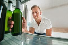 Homem que toma a cerveja de um refrigerador Fotografia de Stock Royalty Free
