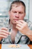 Homem que toma comprimidos Imagens de Stock Royalty Free