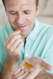Homem que toma comprimidos Fotografia de Stock