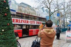 Homem que toma fotos do ônibus turístico da excursão da cidade em seu telefone celular em Berlim, Alemanha fotografia de stock