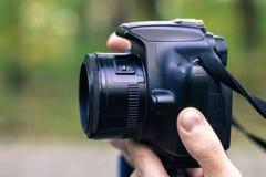 Homem que toma a imagem com câmera de DSLR fotografia de stock
