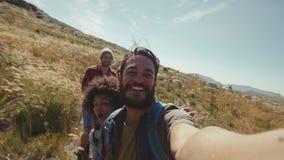Homem que toma a imagem de seus amigos durante a caminhada vídeos de arquivo