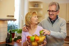 Homem que toma a maçã da bacia de fruta Imagens de Stock Royalty Free