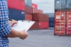 Homem que toma a nota que verifica o transporte de carga na área da jarda do recipiente imagens de stock royalty free