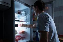 Homem que toma o alimento do refrigerador Foto de Stock Royalty Free
