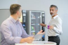 Homem que toma o café da máquina de venda automática foto de stock