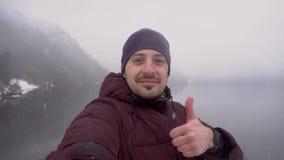 Homem que toma o selfie e que mostra o polegar acima no lago Ritsa na Abkhásia no inverno vídeos de arquivo