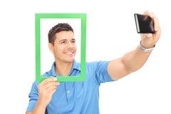 Homem que toma um selfie atrás de uma moldura para retrato Fotos de Stock Royalty Free
