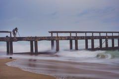 Homem que toma uma fotografia do cais da praia no dia de ataque da chuva imagens de stock