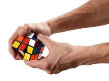 Homem que torce o enigma do cubo de um Rubik imagens de stock