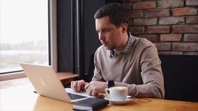 Homem que trabalha com o portátil no café filme