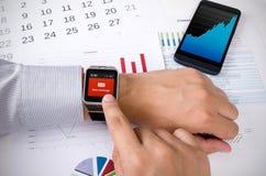 Homem que trabalha com o relógio esperto no escritório Imagens de Stock Royalty Free