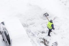 Homem que trabalha com pá a neve após a queda de neve e o blizzard, espaço da cópia Vista superior imagem de stock royalty free