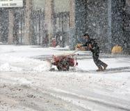 Homem que trabalha com pá a neve durante a tempestade da neve Fotografia de Stock Royalty Free