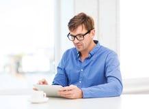 Homem que trabalha com PC da tabuleta em casa fotografia de stock royalty free
