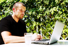 Homem que trabalha com portátil fora Imagem de Stock Royalty Free