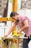 Homem que trabalha com uma máquina de lixar elétrica Fotografia de Stock