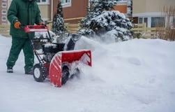 Homem que trabalha com uma máquina de sopro da neve Fotografia de Stock Royalty Free