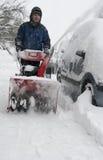 Homem que trabalha com uma máquina de sopro da neve imagens de stock