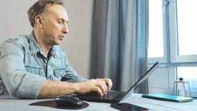 Homem que trabalha em casa em um portátil Vista da parte inferior filme