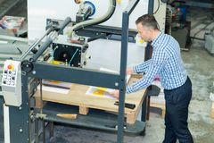 Homem que trabalha em imprimir a fábrica foto de stock