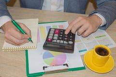 Homem que trabalha na mesa de escritório com calculadora, uma pena e documento Homem, contando o dinheiro e fazendo cálculos imagem de stock